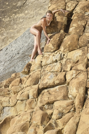 Beautiful nude young woman on the rocks.