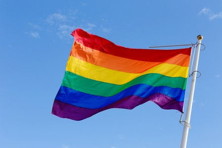 Close-up of a rainbow flag on blue sky.