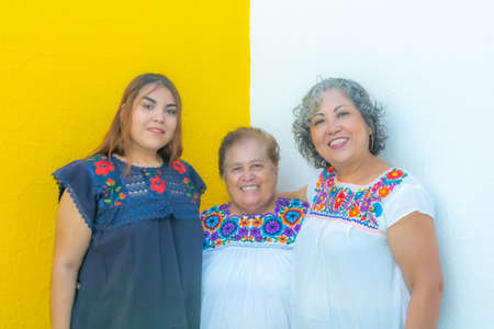 Photo pour Grandmother between daughter and granddaughter very cheerful, three generations of Mexican women smiling with floral printed blouses on a white and yellow background - image libre de droit