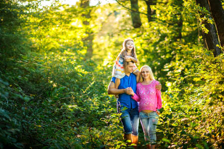 family of three people walks in the evening park, waiting for the child's birth, amicably embrace and pose on the camera, strong family �ŸÑ'�œ�ŸÑˆ�µ�œÑ�, a close-knit family