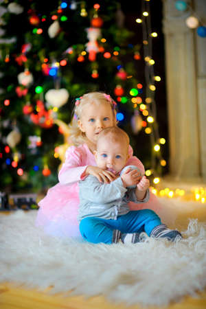 Waiting for Christmas. A happy family, amicably sit on a floor near a New Year tree, embrace and smile. New Year People