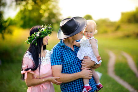 happy family walks in the evening park, amicably embrace and smile