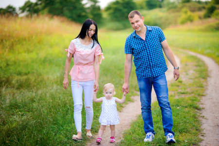 happy family walks in the park, amicably hold hands and smile