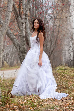 Young woman wearing a wedding dress in a forest