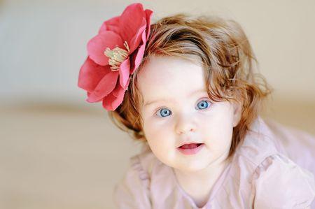 Foto de Cute 9-months baby-girl with flower on her hair smiling - Imagen libre de derechos