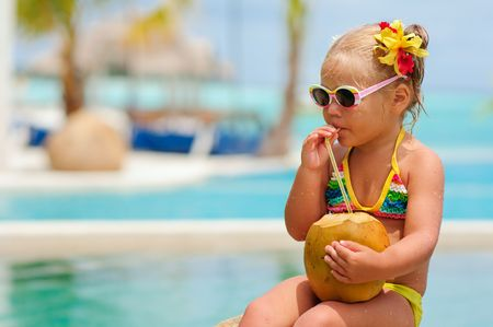 portrait of cute toddler girl with coconut cocktail in the tropical beach