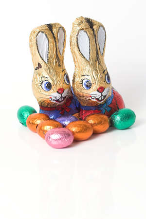 Two easter bunnies made of chocolate surrounded by easter eggs