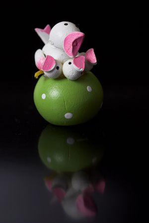 Small easter decoration on black background with reflection