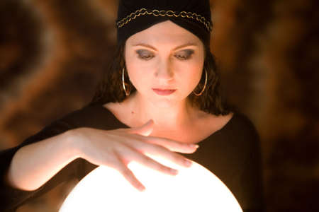 Beautiful gypsy woman with her hand aboe her crystal ball