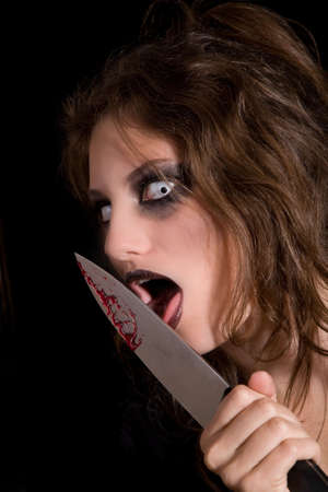 Murderous woman with very scary eyes licking the blood of her knife