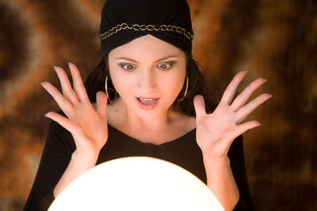 Fortune teller looking very surprised at what she is seeing in her cristal ball