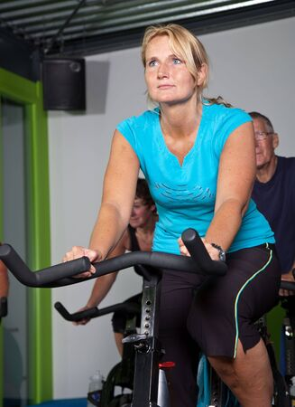 Mature woman doing exercise in spinning class
