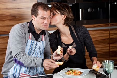 Woman planting a small kiss on her boyfriends cheek for cooking