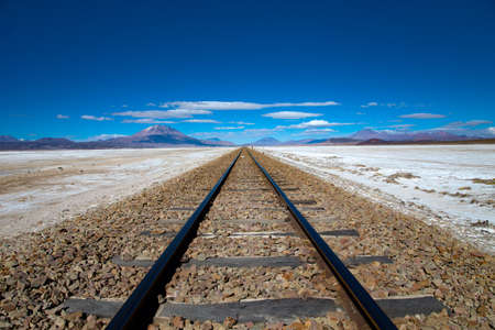 Railroad tracks disappear to the horizon under a bright blue sky