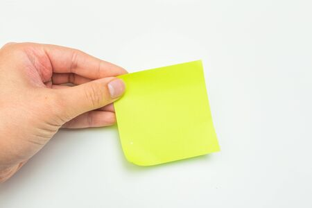 Photo pour Green post-it note with hand on white background - Image - image libre de droit