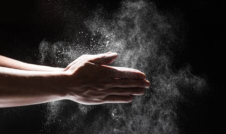 Foto für Powdery flour flying into air as man in black chef outfit wipes off his hands  - Image - Lizenzfreies Bild