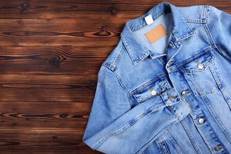 Photo pour blue denim jean jacket  on wooden background - Image  - image libre de droit