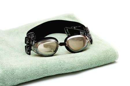 glasses for swim lay on the towel on white