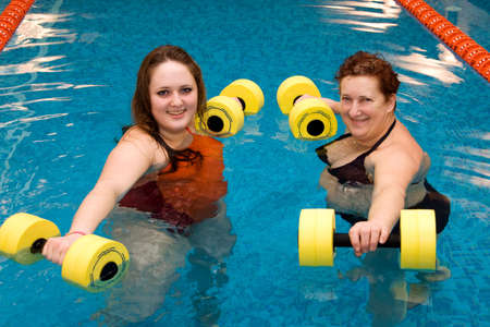 Mum with a daughter are engaged in aqua aerobics