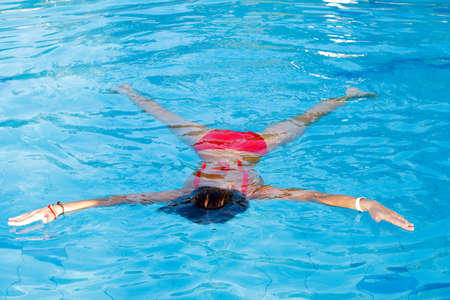 Young woman learn to swimming. Float on the water