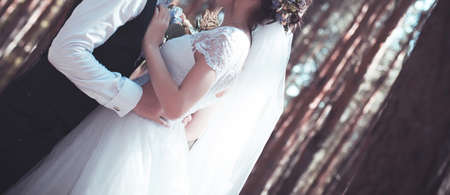 Young pair in strong embraces in the wedding day