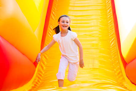 Photo pour Happy little girl having lots of fun on a jumping castle while sliding. - image libre de droit