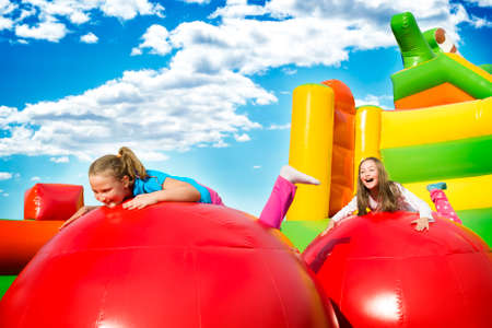 Photo pour Happy little girls having lots of fun while jumping from ball to ball on an inflate castle. - image libre de droit