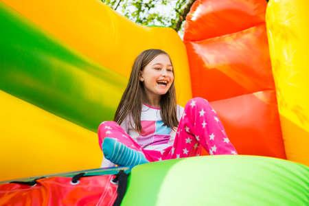 Photo pour Happy little girl having lots of fun on a jumping castle during sliding. - image libre de droit