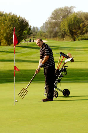 Photo pour Funny Male Golfer Playing Golf With Pitchfork - image libre de droit