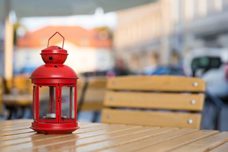 red lantern standing on the wooden table in the city centerの写真素材