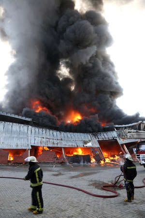 Warehouse building burning with intense flames and fireman attending