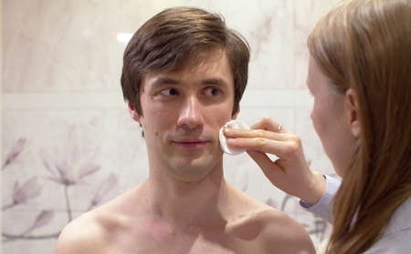 Close up portrait of young handsome man whose wife wipes his face with a cotton pad in the bright bathroom. Male face skin care. Man making funny faces