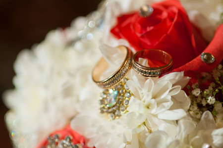 Wedding bouquet of beautiful roses and rings