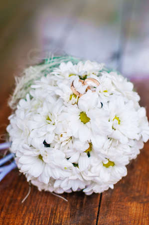 Wedding bouquet of beautiful daisies and rings