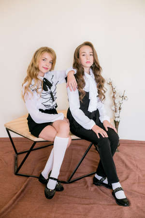 Foto de Two cute girls schoolgirls with long curly hair in fashionable school clothes. School fashion in vintage elite style. - Imagen libre de derechos