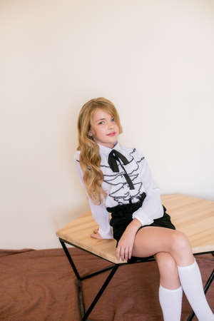 Photo pour Cute girl with long blond curly hair in school fashion clothes. School fashion in vintage elite style. - image libre de droit