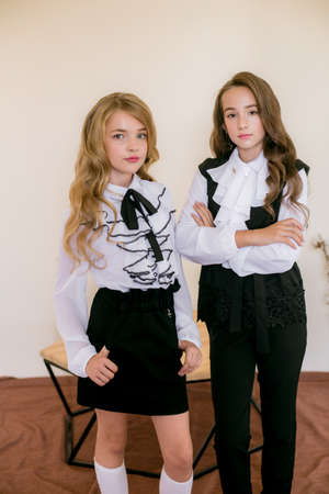 Photo for Two cute girls schoolgirls with long curly hair in fashionable school clothes. School fashion in vintage elite style. - Royalty Free Image