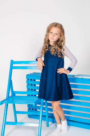 Photo pour Cute girl with blond curly hair in school fashion clothes with blue chair on a white background - image libre de droit