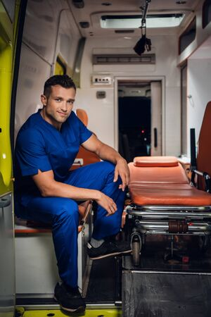 Photo pour Happy paramedic sits in the ambulance car on the background - image libre de droit