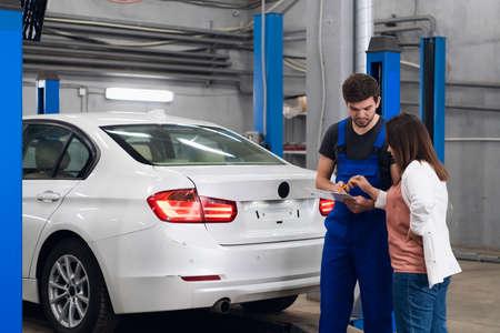Photo pour A car service worker asks a women about a car repair - image libre de droit