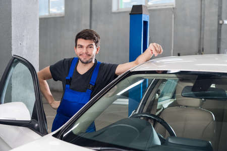 Photo for A man in work clothes is standing next to a white car - Royalty Free Image