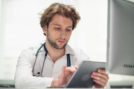 Photo for A young male doctor sitting at his desk in the office, checking the schedule on his tab. - Royalty Free Image