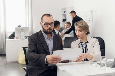 Photo for The Director of the company in a jacket gives instructions and tasks to young colleagues in the office of a trading company - Royalty Free Image