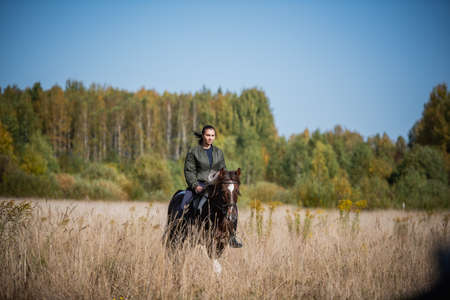 Photo for Cute girl equestrian instructor rides a horse in an equestrian club - Royalty Free Image