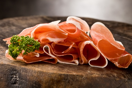 photo of delicious sliced bacon on wooden table with parsley