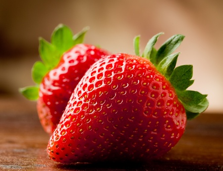photo of delicious strawberries on wooden table in front of brown rustical background