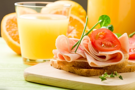 phto of delicious toast with ham on wooden table with orange juiceの写真素材