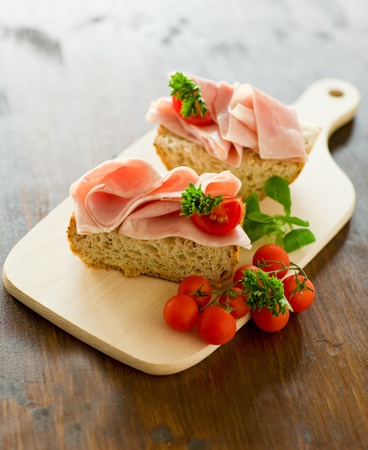 delicious ham tomato sandwich with fresh parsley on wooden table with day light illumination