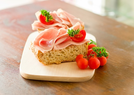 delicicious ham tomato sandwich with fresh parsley on wooden table with day light illumination