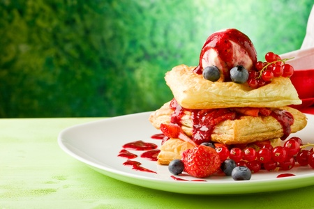 photo of delicious puff pastry with berries and ice cream